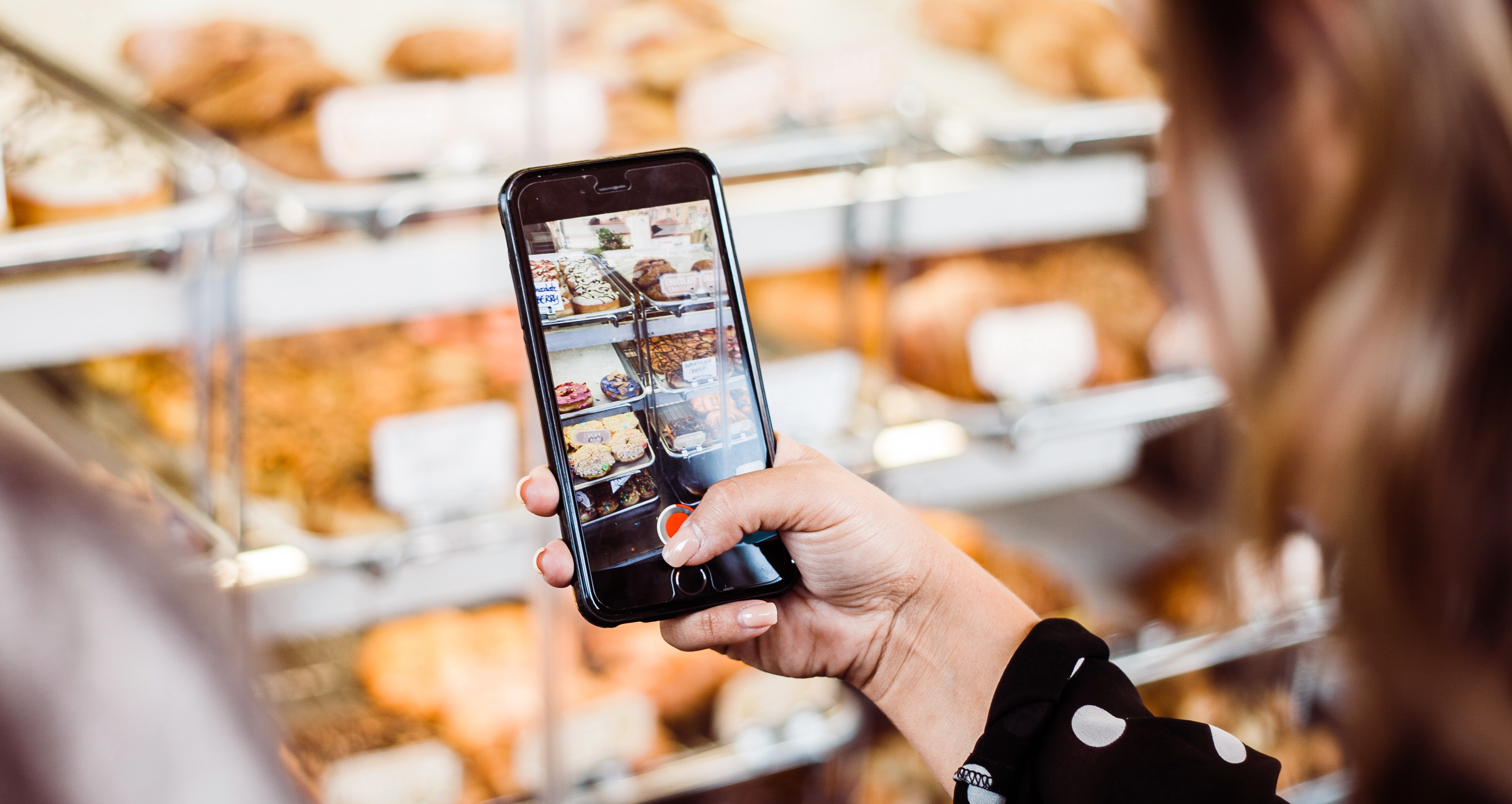 A lady taking an image of cakes and pastries, this image is user-generated content used to improve online reputation